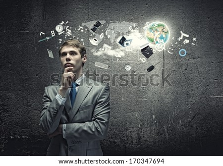 Young thoughtful businessman looking up with hand on chin. Elements of this image are furnished by NASA - stock photo