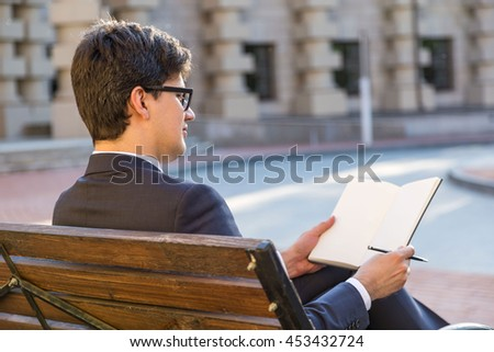 Young thoughtful businessman sitting on outdoor bench and writing in blank notepad
