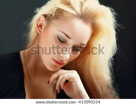 Young thoughtful female looking down over dark background - stock photo