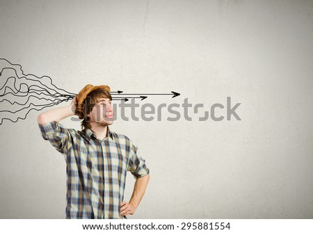 Young thoughtful guy and ideas coming out of his head - stock photo