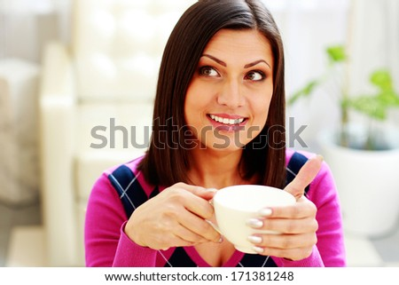 Young thoughtful happy woman holding cup of coffee and looking up