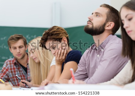 Young thoughtful male university student sitting in a group of students busy studying at a table with his head tilted back as he tries to solve a problem or seek inspiration - stock photo