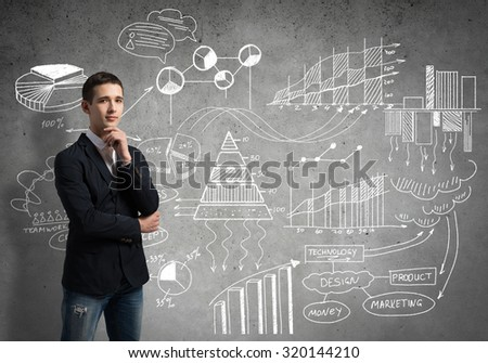 Young thoughtful man and sketches on wall - stock photo
