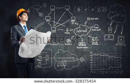 Young thoughtful man engineer in helmet with project in hands and sketches on wall - stock photo