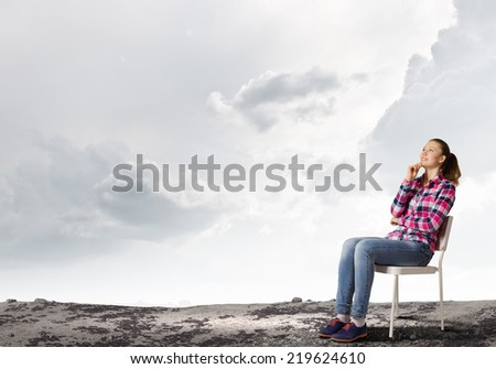 Young thoughtful woman in casual sitting in chair