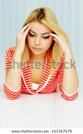 Young thoughtful woman in red jacket sitting at the table - stock photo