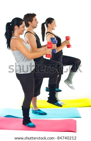 Young three adults doing fitness with barbell and standing on colorful mats - stock photo