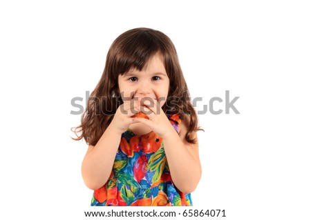 Young three year old girl about to bite a piece of fruit on a white background - stock photo