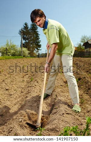 Young tiller working the land with a hoe in a sunny day