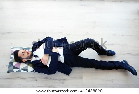 Young tired businessman with a laptop sleeping on the floor - stock photo