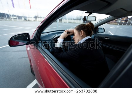Young tired businesswoman sleeping in car - stock photo