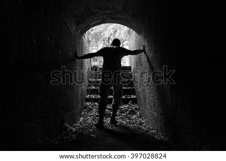 Young tired man leaves dark stone tunnel with glowing end, black and white photo  - stock photo