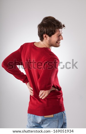 Young tired man suffering from strong backache - stock photo