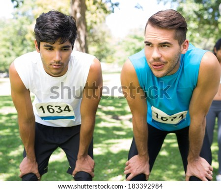Young tired marathon runners with hands on knees standing in park - stock photo