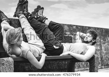 Young tired people friends in training suit with roller skates. Woman and man relaxing lying on bench outdoor.