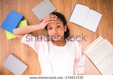 Young tired schoolgirl laying on the floor with some color books. - stock photo