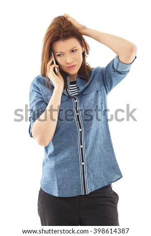 Young tired, stressed woman in blue shirt talk over her mobile phone