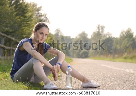 Young tired woman having a rest after jogging outdoors summer time. Heathy lifestyle concept