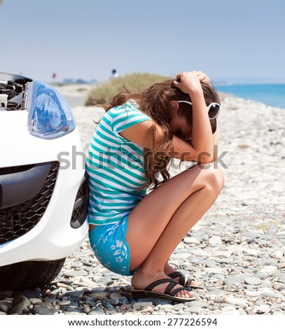 Young tired woman is sitting on the road near broken car - stock photo