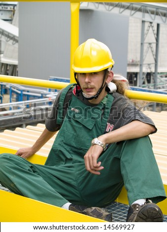 Young tired worker in green uniform in background power statnio.