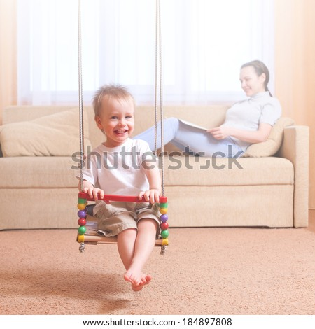 Young toddler boy sitting on a swing. Mother reading