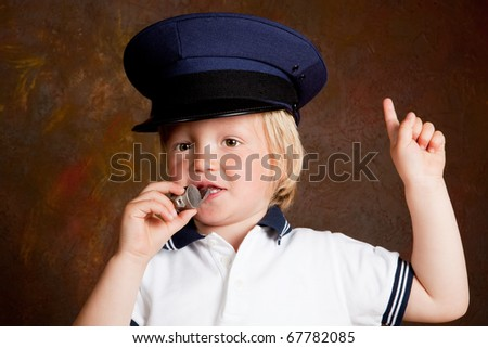 Young toddler boy with police whistle and hat - stock photo