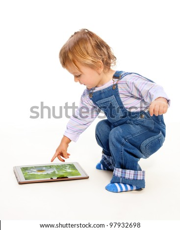Young toddler touching tablet pc (image on the screen from my portfolio) - stock photo