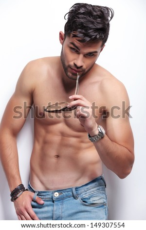 young topless man bitting his sunglasses while looking at the camera. on light gray background - stock photo