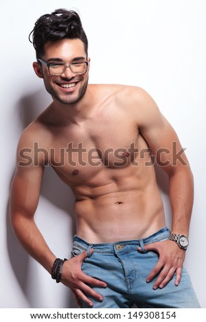 young topless man holding his thumbs in the loops of his jeans and smiling for the camera. on light gray background - stock photo