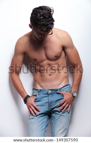 young topless man looking down, away from the camera while holding his thumbs in the loops of his jeans. on light gray background - stock photo