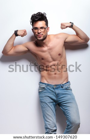 young topless man showing his biceps and abs to he camera. on light gray background - stock photo