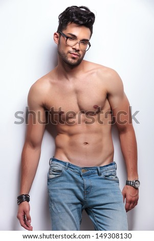 young topless man with eyeglasses looking at the camera. on light gray background - stock photo