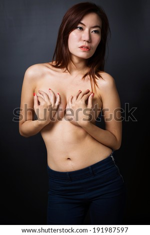 Young topless woman in blue jeans on black background
