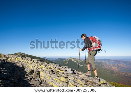 Young tourist backpacker walking on the rocky ridge of the mountain with beautiful high altitude landscape view on the background. Hiker using trekking sticks. autumn. - stock photo