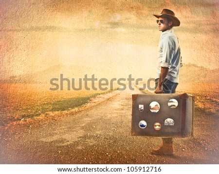 Young tourist carrying a suitcase on a country road at sunset