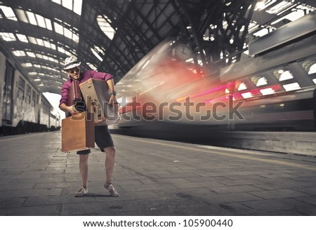 Young tourist carrying many suitcases on the platform of a train station - stock photo