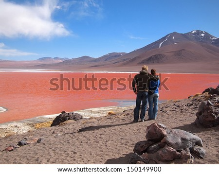 Young tourist couple admiring the Red Lagoon, or Laguna Colorada, on the Altiplano near Uyuni in Bolivia at 4300 m above sea level.  The red color of the water is caused by sediments and algae.