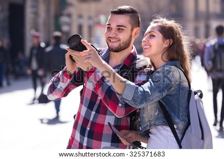 Young tourist couple enjoying excursion and taking pictures outdoors