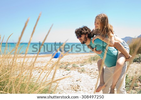 Young tourist couple having fun with man carrying girl on a piggy bag, enjoying a summer holiday together on a beach with clear waters, beach exterior. Travel and lifestyle vacation, nature exterior. - stock photo