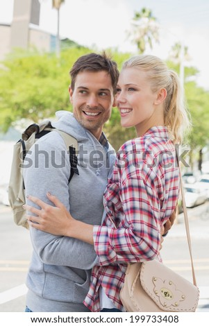 Young tourist couple hugging each other on a sunny day in the city