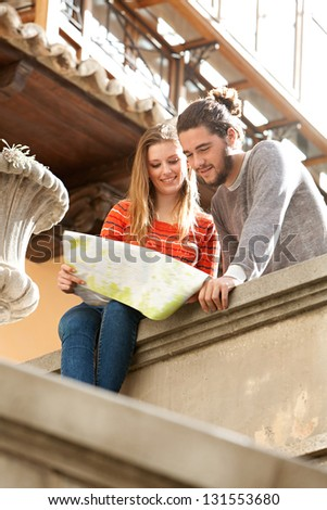 Young tourist couple in a destination city holding a street map looking at directions and interests, relaxing sitting on an old wall, smiling during a sunny day. - stock photo