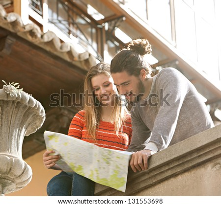 Young tourist couple in a destination city holding a street map looking at directions and interests, relaxing sitting on an old wall, smiling during a sunny day.