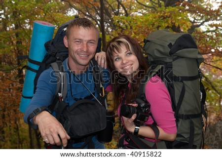 Young tourist couple in the autumn park with rucksacks - stock photo