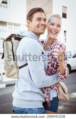 Young tourist couple smiling and pointing at something on a sunny day in the city - stock photo