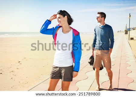 Young tourist couple standing on a beach boardwalk - stock photo