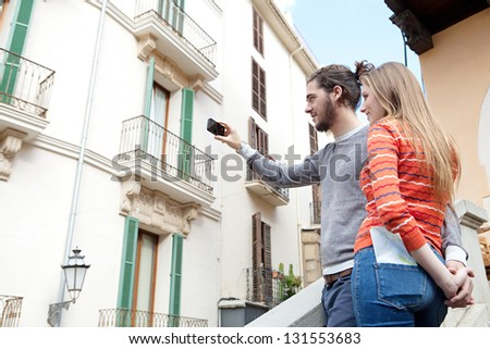 Young tourist couple standing together in a destination city taking pictures of the classic buildings and holding hands during a sunny day.