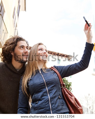 Young tourist couple visiting a destination city and taking pictures of the classic buildings while on vacation in Europe. - stock photo