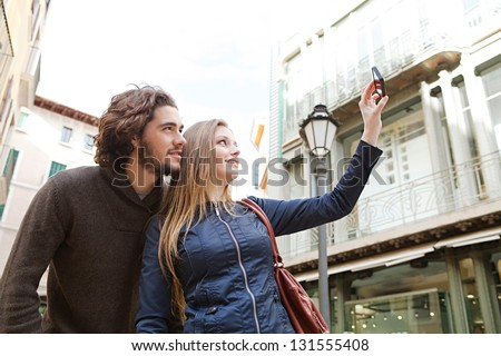 Young tourist couple visiting a destination city and taking pictures of themselves while on vacation in Europe. - stock photo