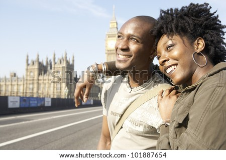 Young tourist couple visiting London's Big Ben, smiling.