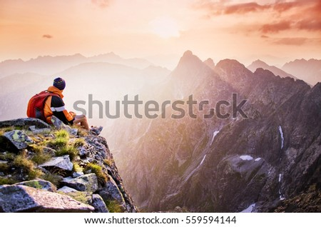 Young tourist, hiker with backpack siting on the top of the hill mountains and looking at beautiful summer sunset